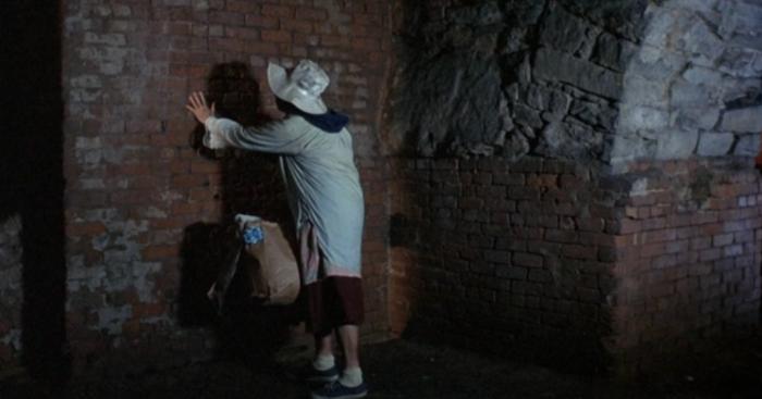 Old bag woman feeling wall in Breeders