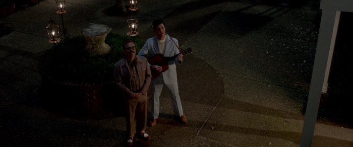 Singing to woman outside of apartment in The Identical