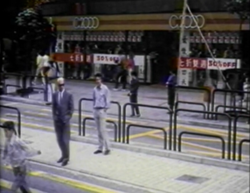 guy following suited man in middle of street