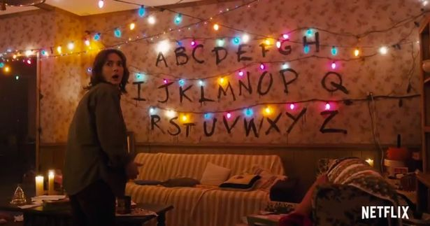 Winona Ryder as Joyce Byers in Stranger Things with light wall